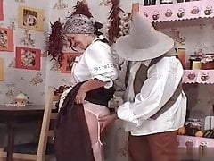 Hungarian gran Ibolya in national clothes drills her grandson