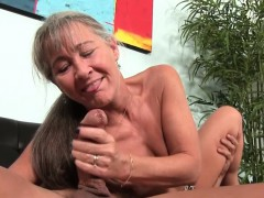 Mature granny stroking dick on couch